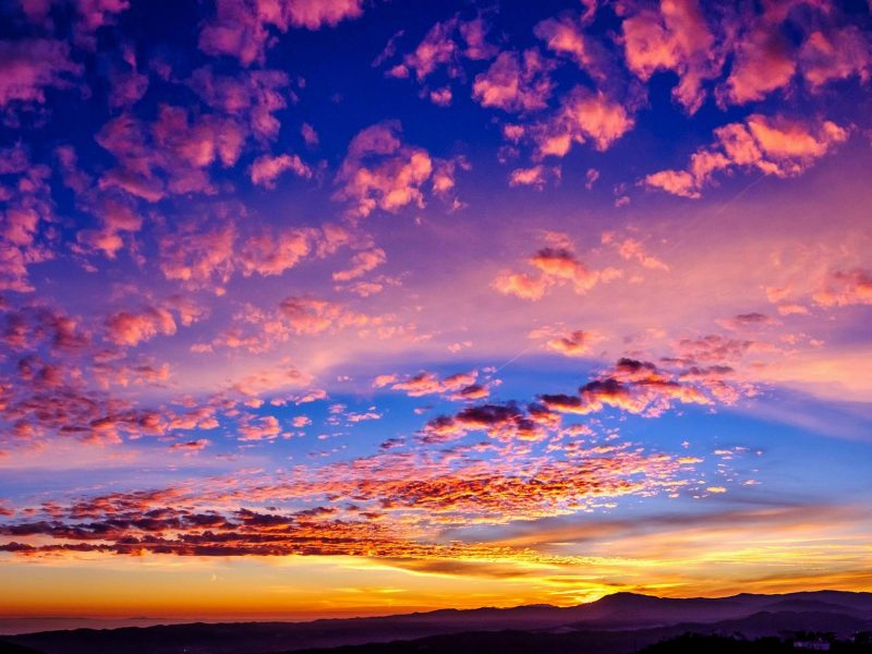 clouds in pink, yellow and orange on a sunset sky